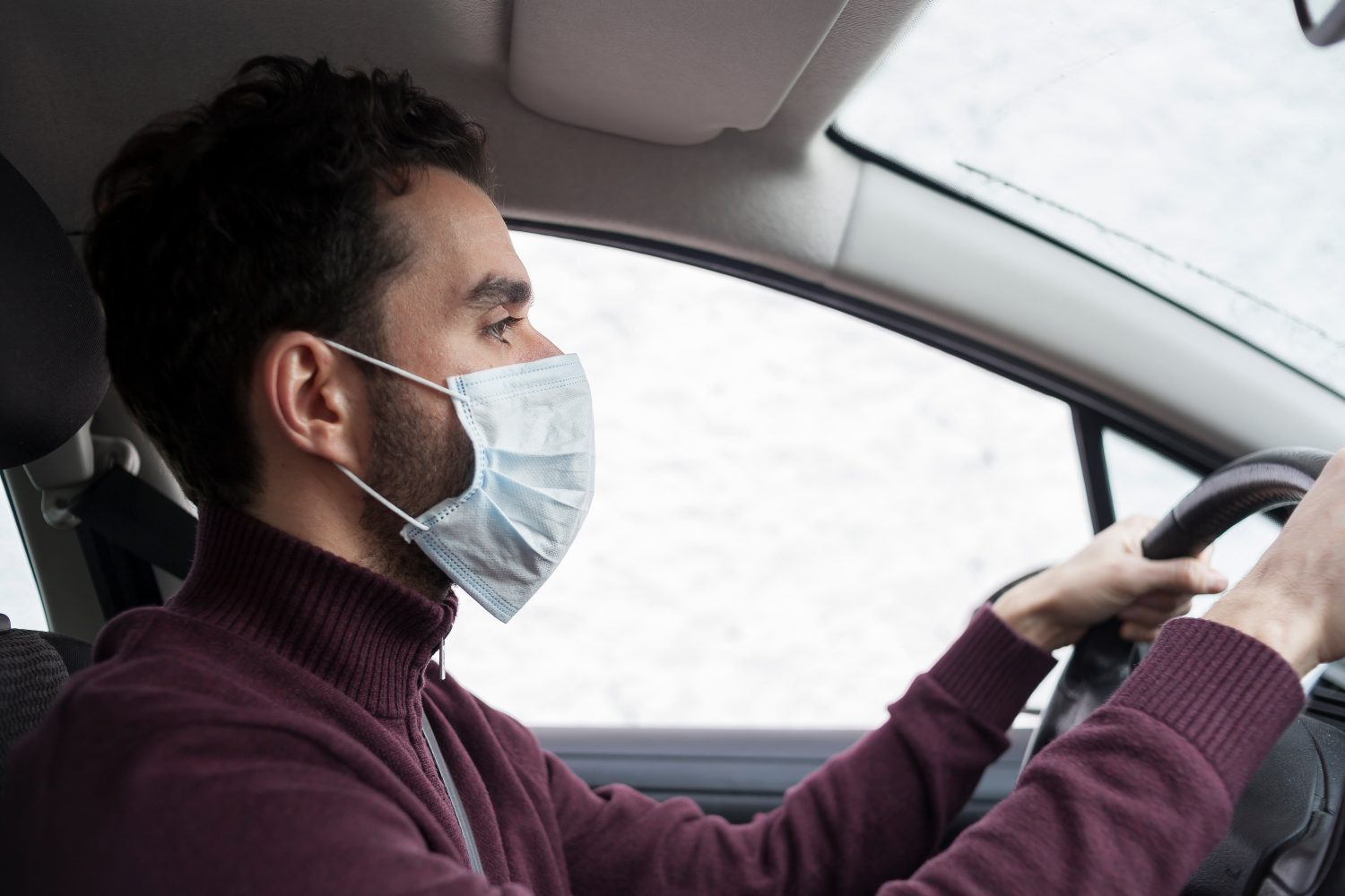 A man driving with a mask